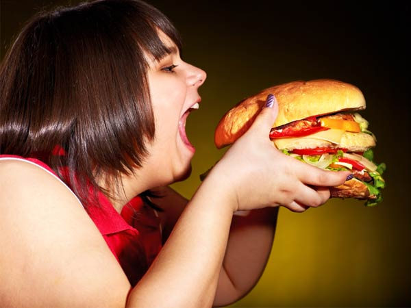 overweight-woman-eating-hamburger-istock
